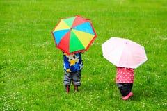 Ungar med färgrika paraplyer på regnig dag royaltyfria foton