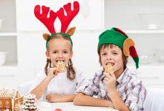 Ungar med julhattar som äter pepparkakakakor Arkivfoto