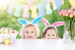 Ungar med kaninöron och ägg på påskägget jagar royaltyfria foton