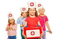 Ungar med medicinska ask- och leksakdoktorsinstrument Arkivbilder