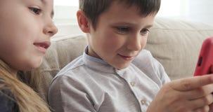 Ungar med mobiltelefonen på soffan lager videofilmer