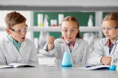 Ungar med provröret som studerar kemi på skolan royaltyfria foton
