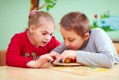 Ungar med speciala behov framkallar deras fina motoriska expertis i daycarerehabiliteringmitt arkivfoto