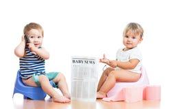 Ungar med tidningen och pda på chamberpot Royaltyfri Bild