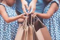 Ungar och föräldern hjälper till att rymma shoppingpåsar Royaltyfria Foton