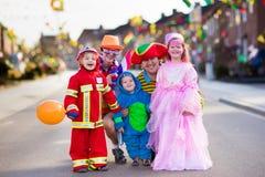 Ungar och föräldrar på allhelgonaaftontrick eller fest royaltyfri fotografi