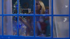 Ungar och kvinna som ut ser i fönster för jul stock video