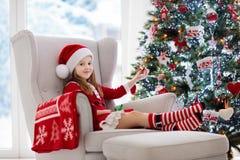 Ungar på julgranen Barn öppnar gåvor fotografering för bildbyråer