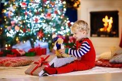 Ungar på julgranen Barn öppnar gåvor arkivfoton