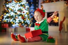 Ungar på julgranen Barn öppnar gåvor royaltyfri foto