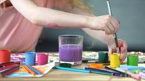 Ungar på målningkurser på konstklubban, flicka som sätter målarpenseln in i vattenexponeringsglas royaltyfria foton