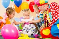 Ungar pojke och flickor med clownen på födelsedag party Fotografering för Bildbyråer