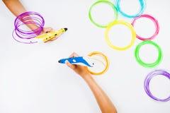 Ungar räcker hållande pennor för printing 3d med glödtrådar på vit bakgrund Top beskådar Royaltyfria Foton