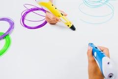 Ungar räcker hållande pennor för printing 3d med glödtrådar på vit bakgrund Top beskådar Royaltyfria Bilder