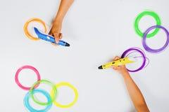 Ungar räcker hållande pennor för printing 3d med glödtrådar på vit bakgrund Top beskådar Arkivfoton