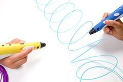 Ungar räcker hållande pennor för printing 3d med glödtrådar på vit bakgrund Top beskådar Arkivbild