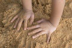 Ungar räcker på sand arkivbilder