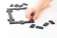 Ungar räcker rymmer en dominobrickategelplatta med royaltyfria foton