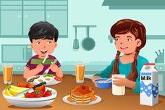 Ungar som äter den sunda frukosten Arkivbilder