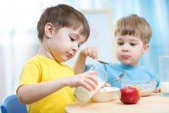 Ungar som äter sund mat i dagis eller barnkammare royaltyfri bild