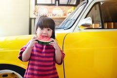 Ungar som äter vattenmelon i sommar Flicka som tycker om hennes söta frukt arkivbilder