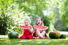 Ungar som äter vattenmelon i trädgården royaltyfria bilder