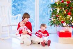 Ungar som öppnar julklappar royaltyfria bilder