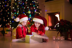 Ungar som öppnar julklappar på spisen Fotografering för Bildbyråer