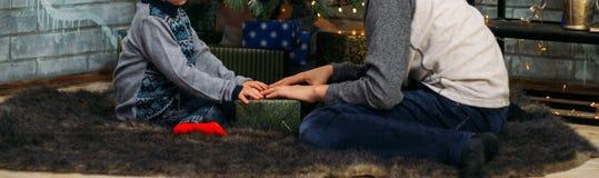 Ungar som öppnar Xmas-gåvor Barn under julgranen med gåvaaskar Dekorerad vardagsrum med det traditionella brandstället cozy royaltyfri foto
