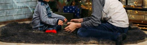 Ungar som öppnar Xmas-gåvor Barn under julgranen med gåvaaskar Dekorerad vardagsrum med det traditionella brandstället cozy royaltyfria bilder