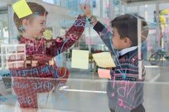 Ungar som affärsledare som till varandra ger höjdpunkt fem nära whiteboard Fotografering för Bildbyråer