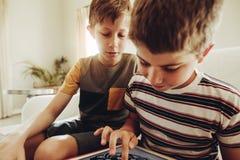 Ungar som använder minnestavlaPC:n för att lära konst royaltyfria bilder
