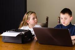 Ungar som arbetar på den gamla skrivmaskinen och bärbara datorn Arkivfoton
