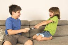 Ungar som argumenterar för att spela med en digital minnestavla Arkivbild