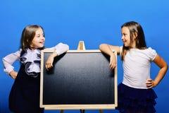 Ungar som bär skolakläder, lutar på den skinande svart tavla royaltyfria foton