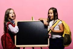 Ungar som bär skolväskor, lutar på den skinande svart tavla, kopieringsutrymme fotografering för bildbyråer