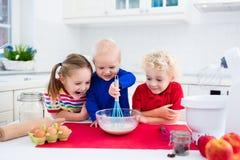 Ungar som bakar en paj i vitt kök arkivfoton