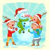 Ungar som bygger snögubben för jul Arkivfoto