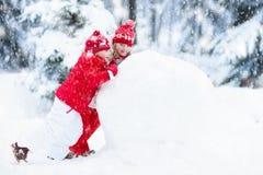 Ungar som bygger snowmanen Barn i snow körning av rolig pulkavinter Arkivbild