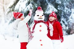 Ungar som bygger snowmanen Barn i snow körning av rolig pulkavinter Fotografering för Bildbyråer