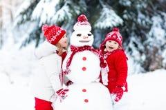 Ungar som bygger snowmanen Barn i snow körning av rolig pulkavinter Royaltyfri Foto
