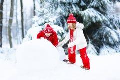 Ungar som bygger snowmanen Barn i snow körning av rolig pulkavinter Royaltyfri Fotografi