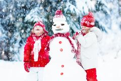 Ungar som bygger snowmanen Barn i snow körning av rolig pulkavinter Arkivbilder