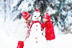 Ungar som bygger snowmanen Barn i snow körning av rolig pulkavinter Arkivfoto