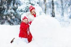 Ungar som bygger snowmanen Barn i snow körning av rolig pulkavinter Royaltyfria Bilder