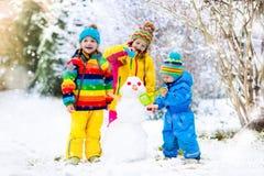 Ungar som bygger snowmanen Barn i snow körning av rolig pulkavinter Arkivfoton