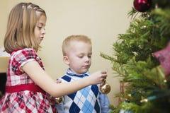 Ungar som dekorerar en julgran Royaltyfri Foto