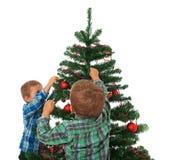 Ungar som dekorerar jultreen Arkivfoto