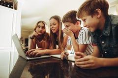 Ungar som delar kunskap genom att använda teknologi royaltyfria foton