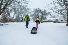 Ungar som drar en släde ner en snö, täckte den förorts- gatan royaltyfri foto